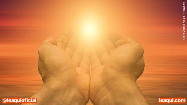 Mãos postas recolhendo uma luz que se aproxima, mostrando o poder das orações