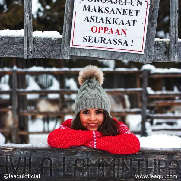 uma moça de blusa vermelha apoiada nos braços cruzados sob uma cerca de um local onde país mais feliz do mundo