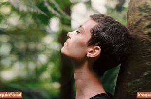 mulher de perfil encostada em uma arvore respiração profunda