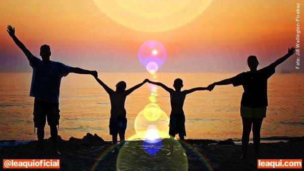 família de mão dadas na praia sob luz atmosfera espiritual