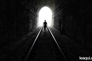 uma pessoa dentro de um túnel escuro caminhando em direção à luz otimismo e entusiasmo