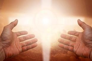 mãos com as palmas para cima em posição para receber a Luz que fortemente à frente brilha em um centro espírita