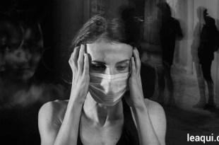 mulher de máscara cirúrgica com as mãos apoiando a cabeça tendo à sua volta imagens de obsessores meio-obsessões dos quase-obsidiados