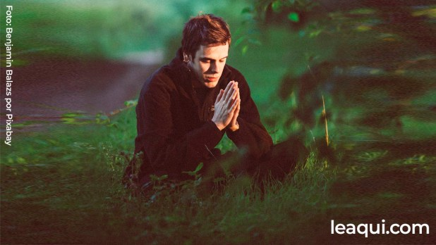 rapaz sentado em um belo bosque com as mãos postas em oração proteger pensamentos alheios