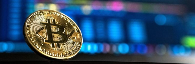 Physical bitcoin in front of a trading screen