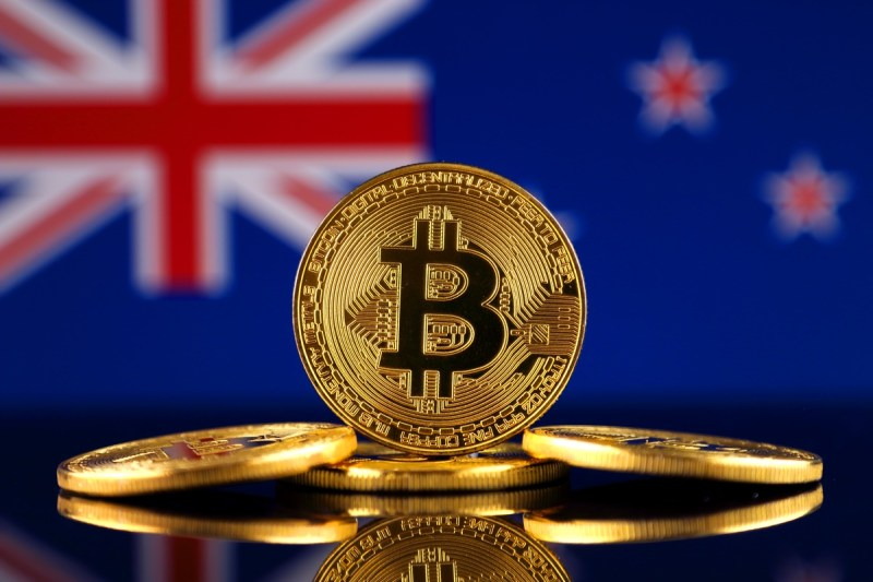 Stack of gold bitcoins in front of the New Zealand flag