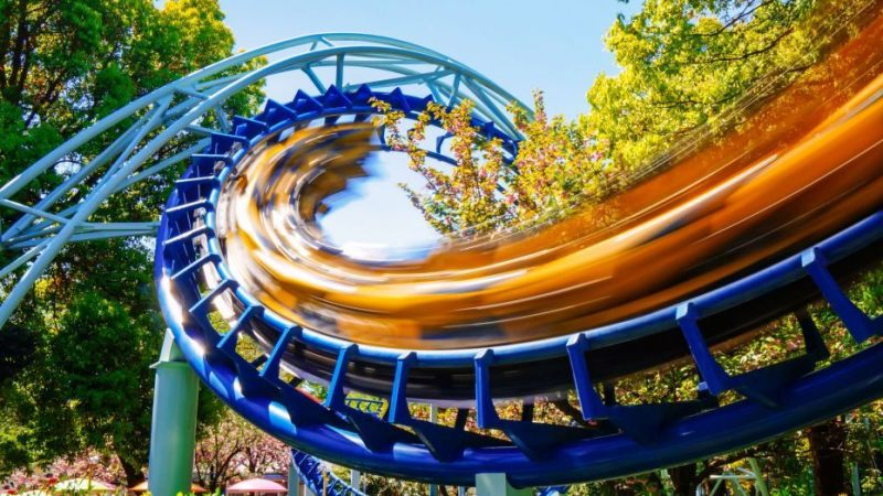 Roller coaster going fast on blue tracks with blue sky in background