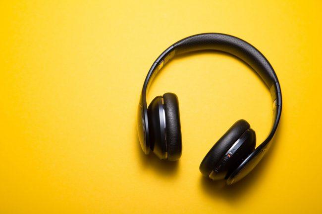 black over head headphones against yellow background
