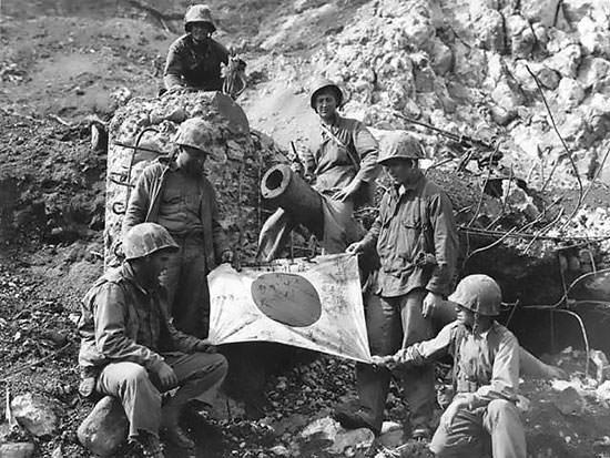 U.S. Marines with captured Japanese flag