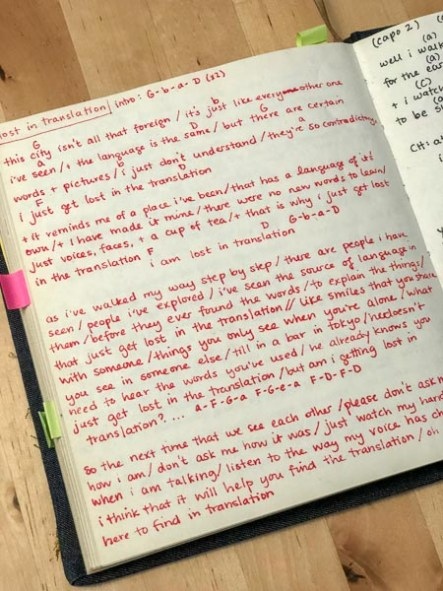 Open page of songbook with handwritten song lyrics, chords and notes