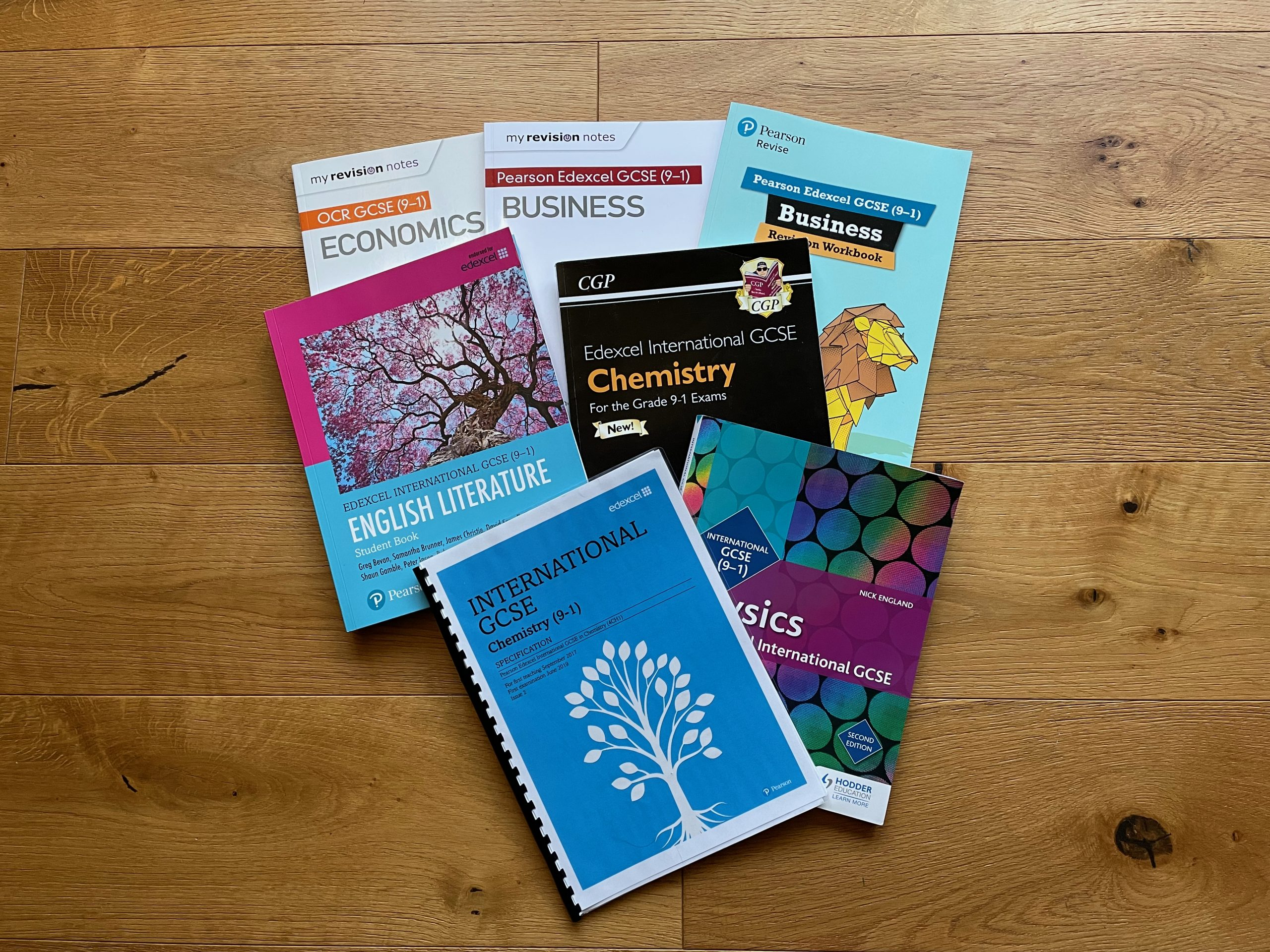 selection of GCSE textbooks lying on a wooden floor