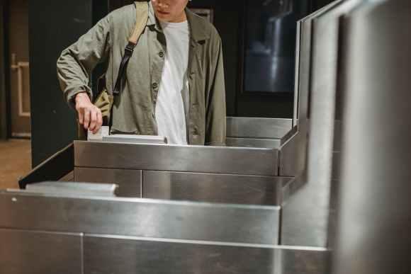 crop man using card to enter city subway gate