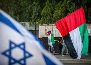 A man waves a giant United Arab Emirates flag outside the Prime Minister's official residence in Jerusalem on August 19, 2020. Photo by Yonatan Sindel/Flash90 *** Local Caption *** ????? ????????? ??? ??? ??????? ????? ??? ?????? ?????