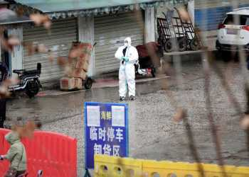 FILE PHOTO: A worker in a protective suit is seen at the closed seafood market in Wuhan, Hubei province, China January 10, 2020. Picture taken January 10, 2020. REUTERS/Stringer/File Photo/File Photo