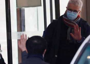 Dominic Dwyer, a member of the World Health Organisation (WHO) team tasked with investigating the origins of the coronavirus disease (COVID-19), waves as they leave their quarantine hotel in Wuhan, Hubei province, China January 28, 2021. REUTERS/Thomas Peter