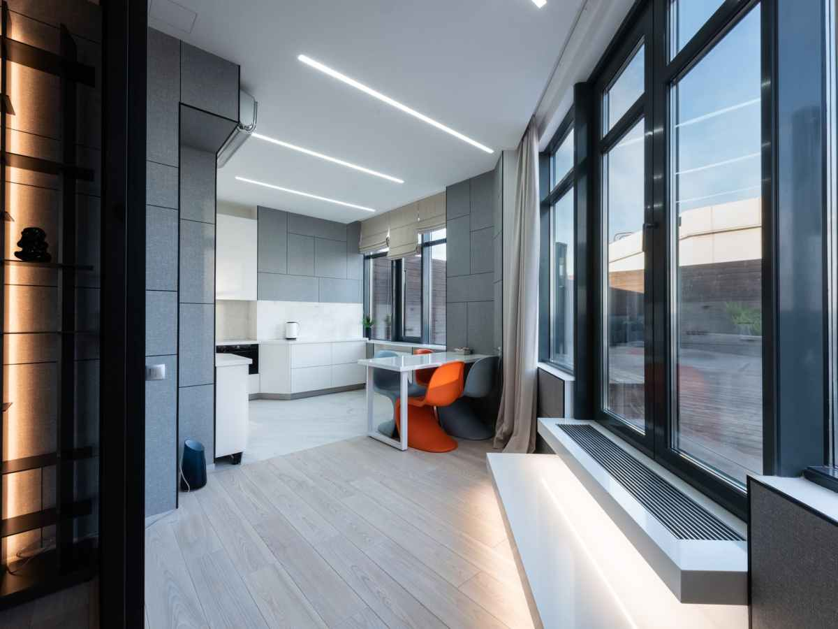 interior of modern apartment with window and kitchen near table