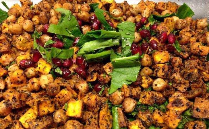 Salat aus gerösteten Kichererbsen und Süßkartoffeln mit Spinat, Granatapfelkernen und Tahini-Dressing