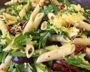 Italienischer Nudelsalat mit Tomaten, Oliven, Rucola und Pinienkernen