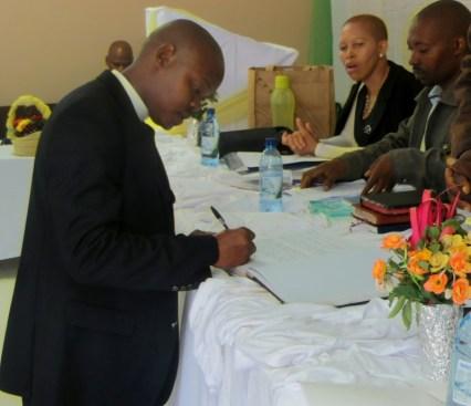 Rev. R. L. Moloi signing the register