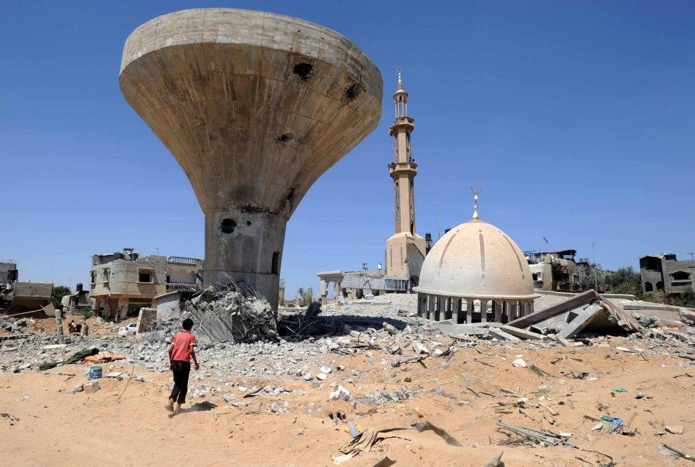 Agosto 2014. Palestino buscando, trás los bombardeos del ejército israelí, entre las ruinas de casas destrozadas en Khuzaa, este de Khan Younis, franja de Gaza. © Archivo fotográfico de UNRWA (Agencia de la ONU que se ocupa de los refugiados palestinos)