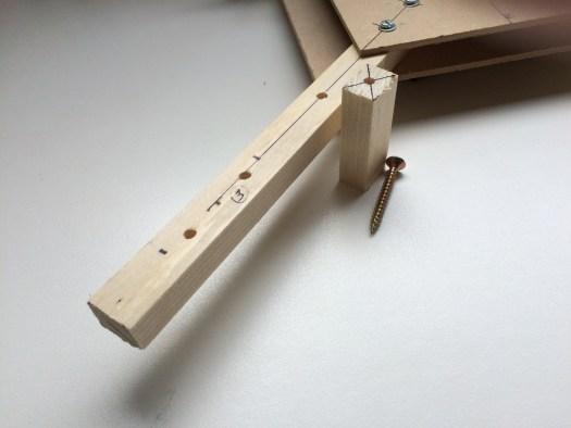 Un pied en bois est placé à 12 cm du bord sur chaque bras. Ca permet de réaliser un train d'atterrissage à moindres frais.