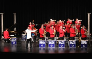 The Glenn Miller orchestra performs on stage. A band leader stands before brass, woodwinds, and a piano player.