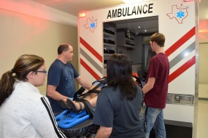Students practice loading patient into ambulance