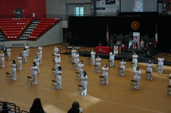 Nursing graduates in white uniforms standing in an arena next to chairs holding symbolic lamps.