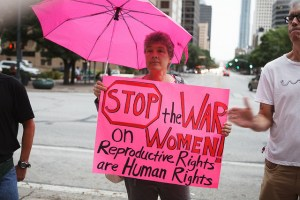 """Woman holds pink sign that reads """"Stop the War on Women: Reproductive Rights are Human Rights"""", as she stands under a pink umbrella"""