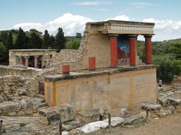 The partially restored North Portico of the palace at Knossos in Crete. A restoration of one of the palace's many bull frescoes can be seen on the wall behind the red columns.