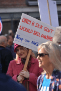 """carrying a banner which says """" only a sick government would sell our NHS, Keep our NHS Public"""""""