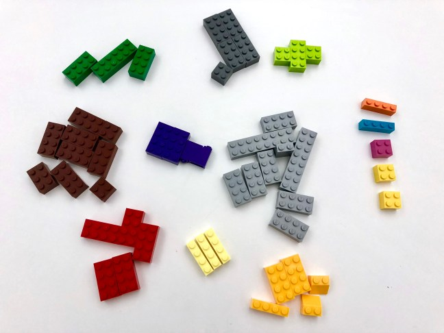 LEGO bricks grouped into piles of the same colour. Some to the right are discarded.