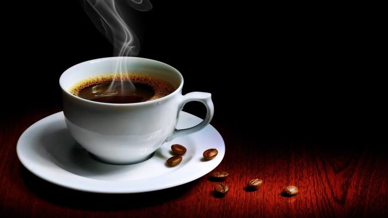 Tasse de café fumante avec quelques grains de café à côté