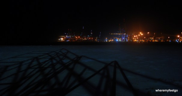 a flat area of sand with the shadows of a play structure across it. background has many lights and crane type things that are part of the freeport