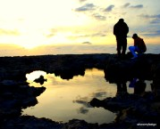 the sky and setting sun reflected in an oddly shaped puddle. two people are in the background, silhouetted against the sky. one is standing one is crouching.