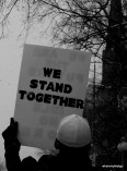 "a white sign with black letters saying ""we stand together"""
