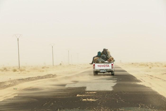 Tempête de sable sur la route vers Nouadhibou. Ciel blanc, grand vent et sable fin... Hommes et Femmes sont souvent entièrement couverts pour se protéger dans le désert. Le 2 Janvier 2019. Crédit : Lison Bourgeois. Retouche : Marie Solvignon.
