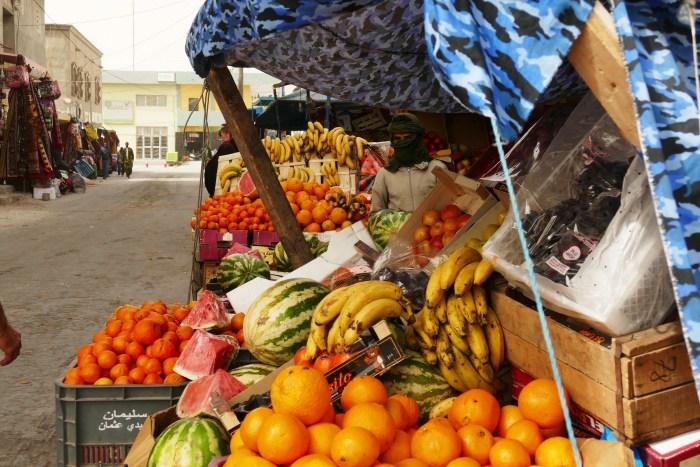 Scène de marché à Nouadhibou. Même en ville les hommes sont aussi couverts pour se protéger du vent, du sable et du soleil. Le 19 Décembre 2019. Crédit : Lison Bourgeois. Retouche : Marie Solvignon.