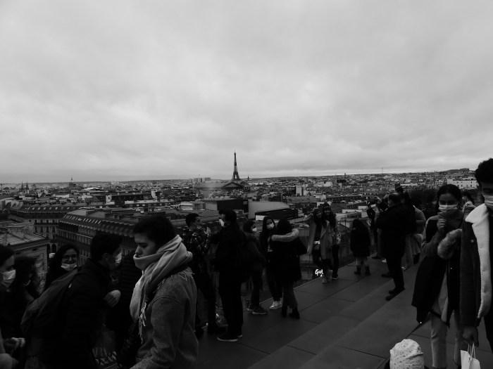 Sur le toit des Galeries Lafayette, les touristes se réunissent, masqués, pour profiter d'un panorama de la ville de Paris où la Tour Eiffel ressort fièrement. La capitale, l'une des villes les plus visitées du monde, ne perd donc pas entièrement son attrait touristique. Photo : Antoine Allart