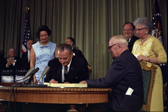 President Lyndon B. Johnson signs the Medicare Bill at the Harry S. Truman Library in Independence, Missouri, in 1965. Truman is seated at the table with Johnson.