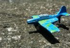 Blue and green plane toy on concrete pavement