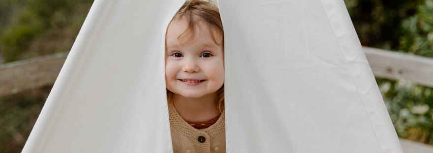 happy little child smiling while peeking from tent