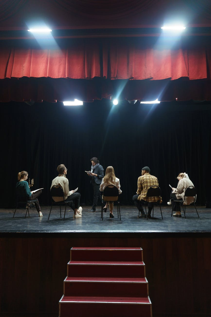 group of people sitting on chair on stage