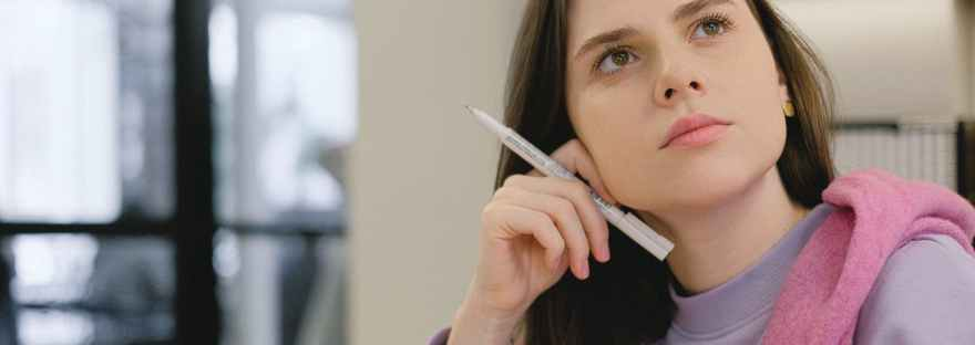 smart young female student looking away thoughtfully during lesson in college