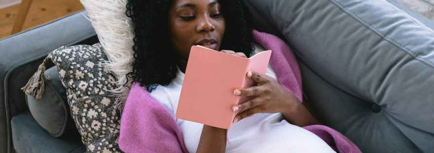 black pregnant woman writing in notebook on couch