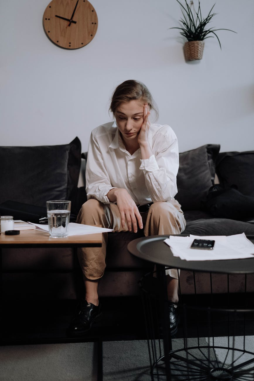 a woman with problems sitting on the sofa