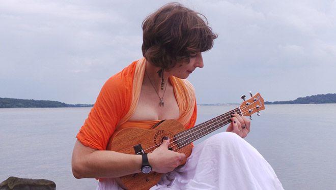 Meisje aan de kust met ukulele