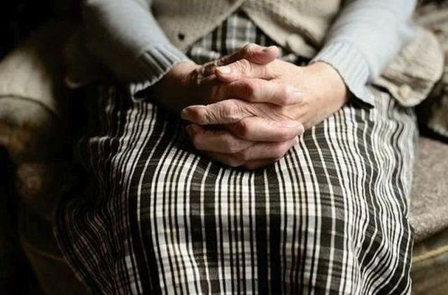 Femme en maison de retraite, les mains croisées