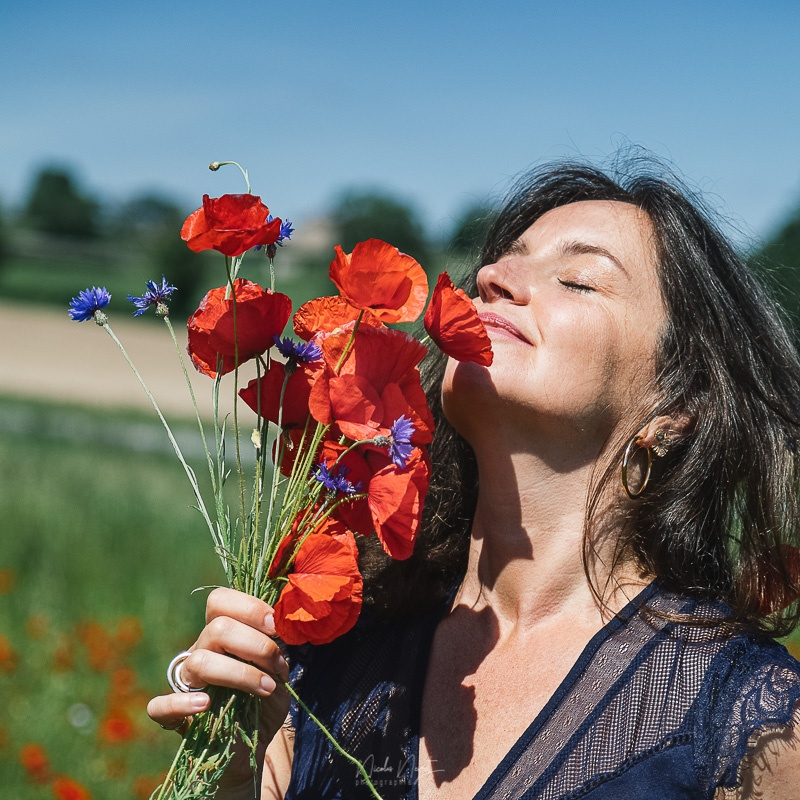 Marie Rouyat sentant un bouquet de fleurs. Thérapeute et naturopathe au sein de Le Goût des Cerises spécialisé dans le développement personnel et psychothérapeute à Saint-Pierre-des-Corps.