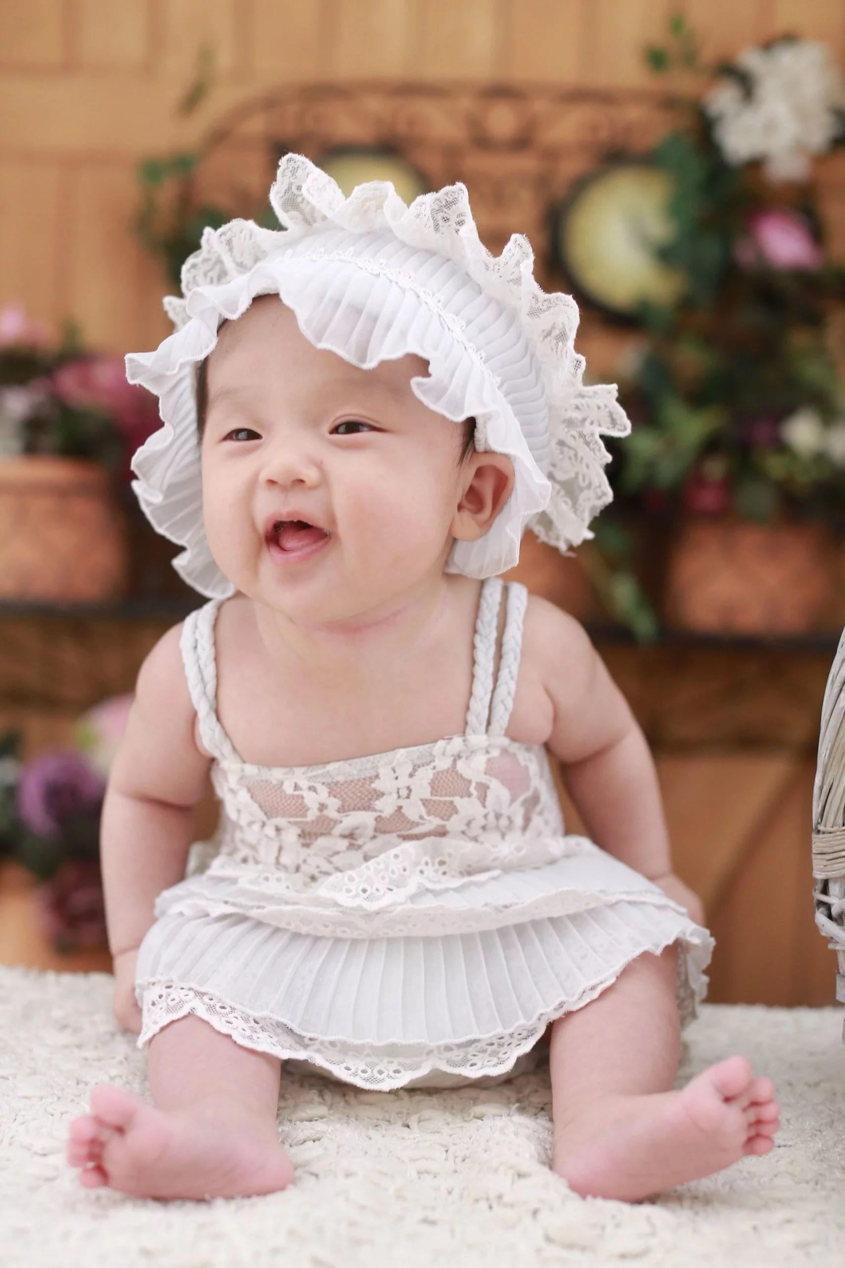 """Bébé fille asisatique habillée avec une robe blanche, représentant le deuxième module """"Le corps de naissance d'une Femme"""" proposé dans le stage de la saison des femmes par Le Goût des Cerises à Saint-Pierre-des-Corps."""